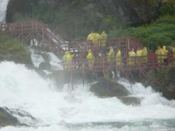 Tourists in yellow raincoats on stairs next to Bridal Veil Falls as viewed from Maid of the Mist.jpg